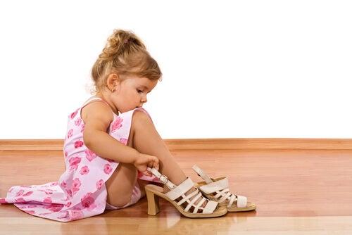 annesinin topuklu ayakkabılarını giymeye çalışan kız bebek