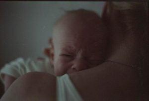 ağlayan bebeğini tutan anne