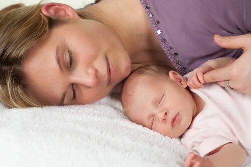uyurken annesinin parmağını tutan bebek