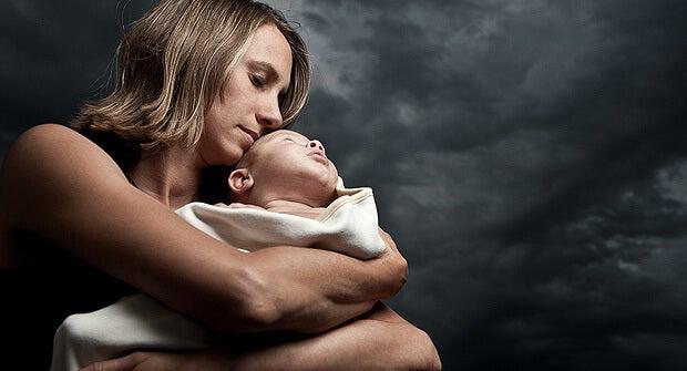 bebeğine sıkı sıkı sarılan anne
