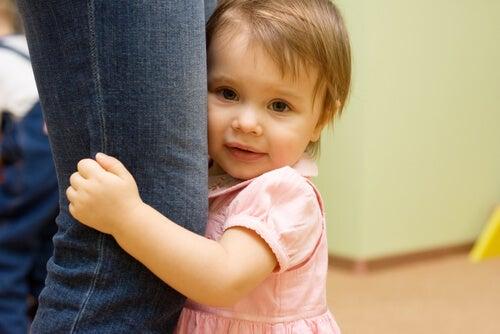 annesinin bacağına sarılan bebek