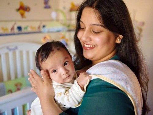 yenidoğan oğlunu omzunda tutan anne