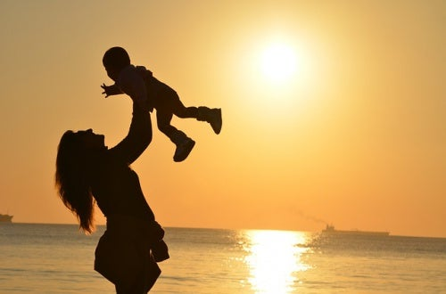 gün batımı fonunda bebeğini havaya kaldıran anne