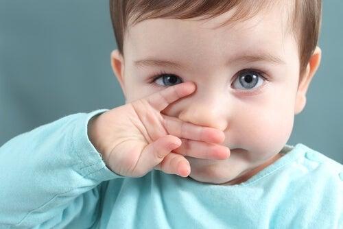 burnunu tutan mavi gözlü bebek