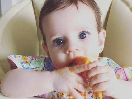 eliyle yemek yiyen bebek