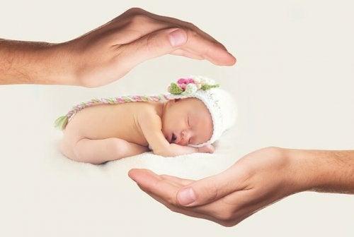 anne elleri arasında bebek figürü