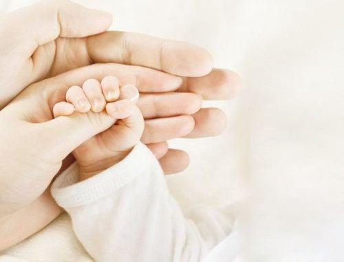 bebeğinin parmağını tutan anne