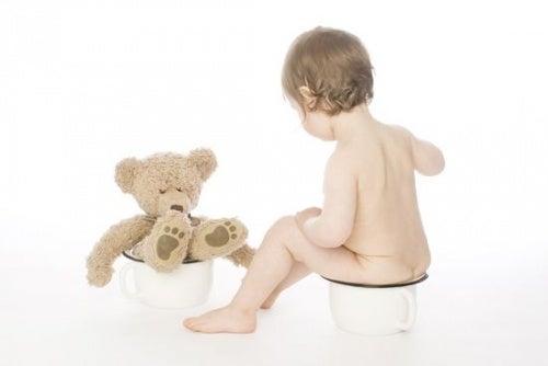 oyuncak ayısıyla lazımlıkta oturan bebek