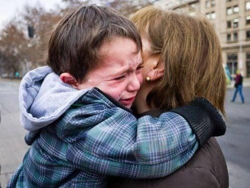 ağlayan çocuğuna sarılan anne