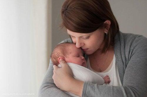 Uyuyan bebeğini göğsünde tutan anne