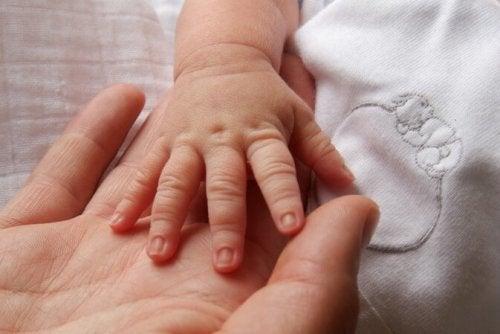 Elini annesinin eline koymuş bebek