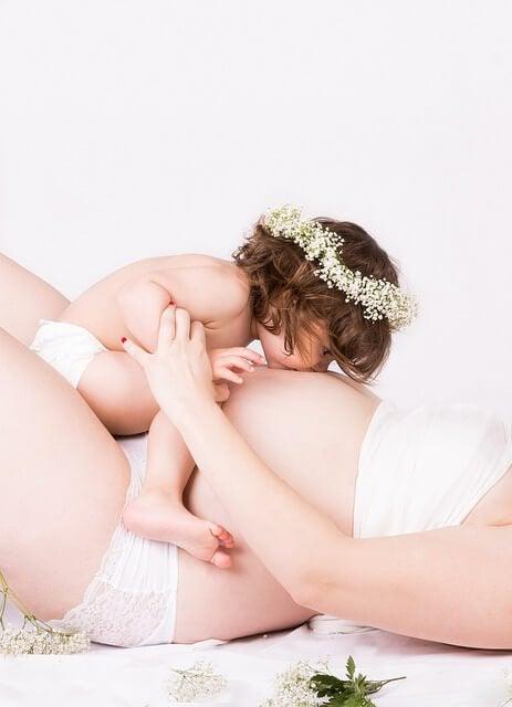annesinin hamile karnını öpen bebek