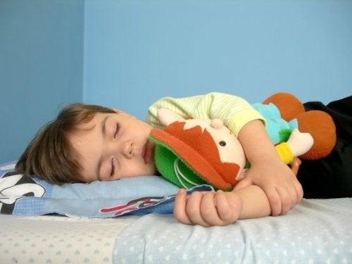 oyuncağına sarılıp uyuyan çocuk