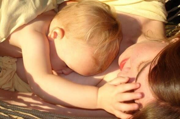 güneşte yatan anne ve bebek