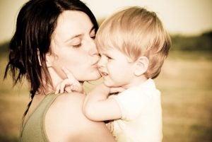çocuğunu yanağından öpen anne