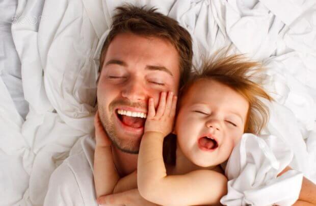 babasının yüzünü tutan bebek