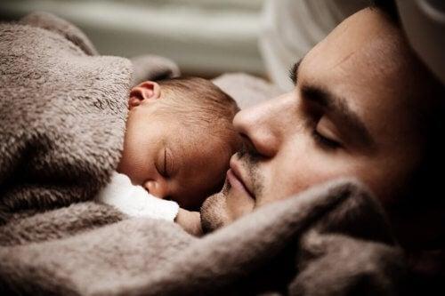 babasıyla uyuyan yenidoğan