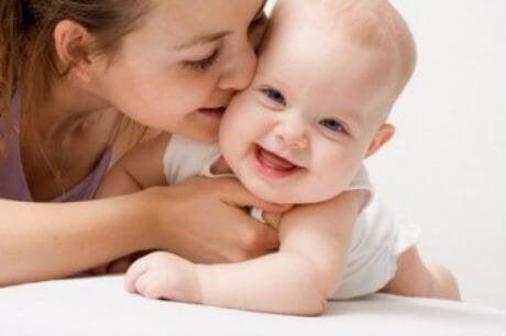 gülen bebeğini öpen anne