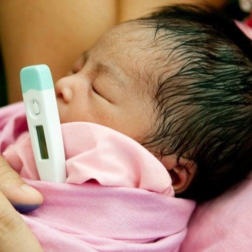 dereceyle ateşi ölçülen bebek