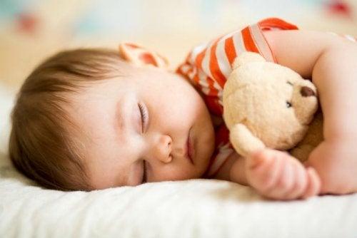 oyuncak ayısıyla uyuyan çocuk