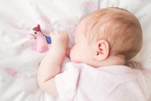 elinde oyuncağıyla uyuyan bebek