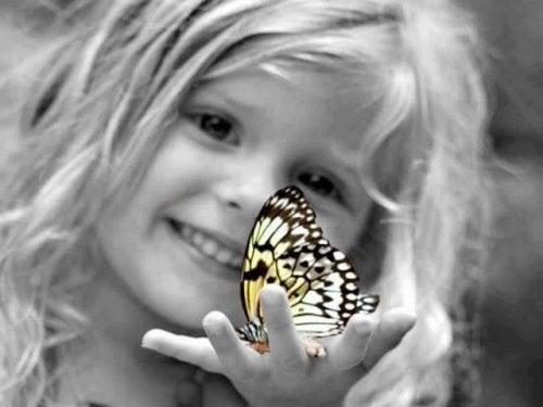 elinde kelebek tutan kız çocuğu