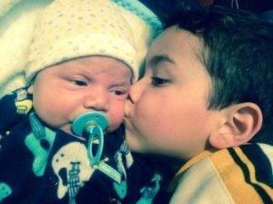 kardeşini öpen bebek