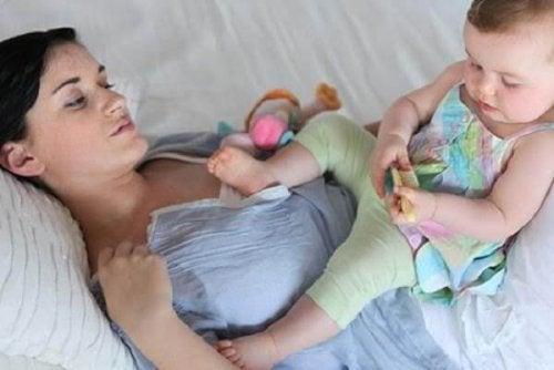 kucağında bebeğiyle yatakta anne