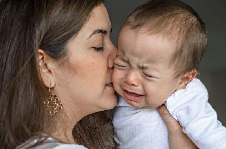 ağlayan bebeğini öpen anne