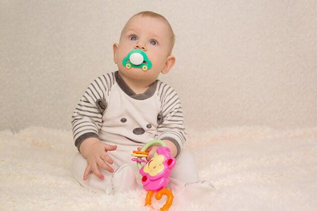 ağzında emzik ve oyuncağıyla bebek