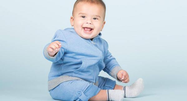 oturan mavi kıyafetli bebek