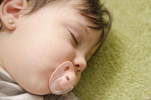ağzında emzik uyuyan kız bebek