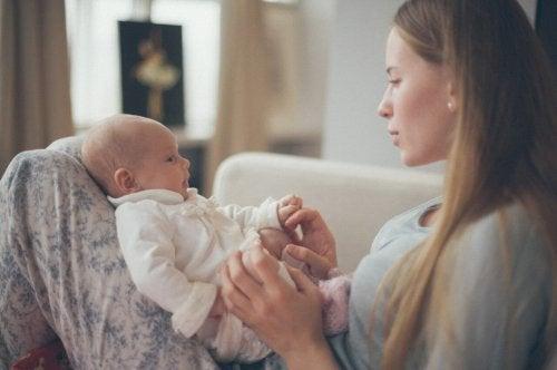 kucağında yenidoğanıyla oynayan anne