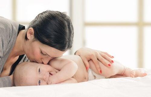 yanağından bebeği öpen anne