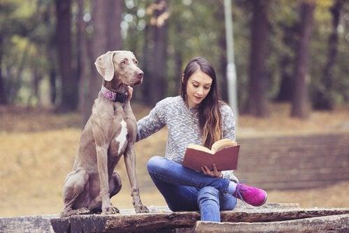 köpeğiyle kitap okuyan kız