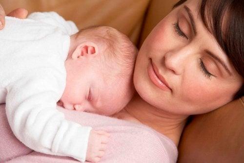bebeğine sarılmış uyuyan anne