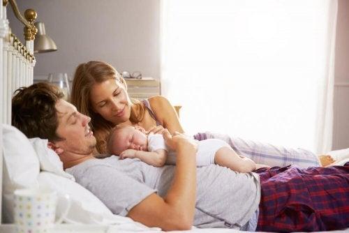 yenidoğanlarıyla yatakta aile