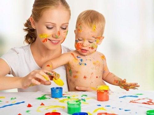 Annesiyle boya yapan bebek