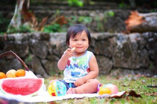 bahçede meyve yiyen çocuk