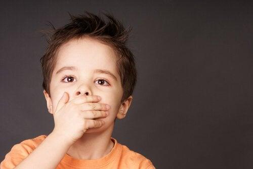 Ağzını kapatan erkek çocuk