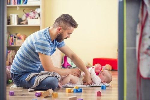 baba çocuğun altını temizliyor
