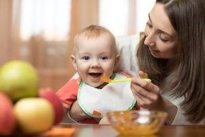 Annesi bebeğe meyve püresi yediriyor