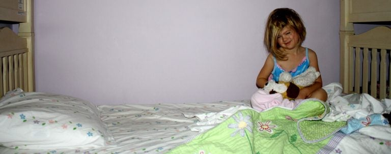 yatağın köşesinda oturan kız çocuğu