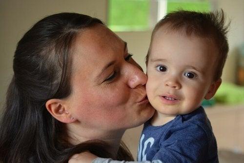 bebeğini yanağından öpen anne
