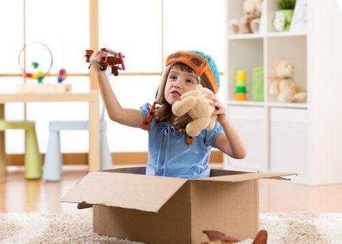 karton kutuda kendin yap oyuncaklarıyla oynayan çocuk