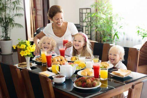 anne ve üç çocuk masada oturuyorlar sonbaharda önerilen vitaminler