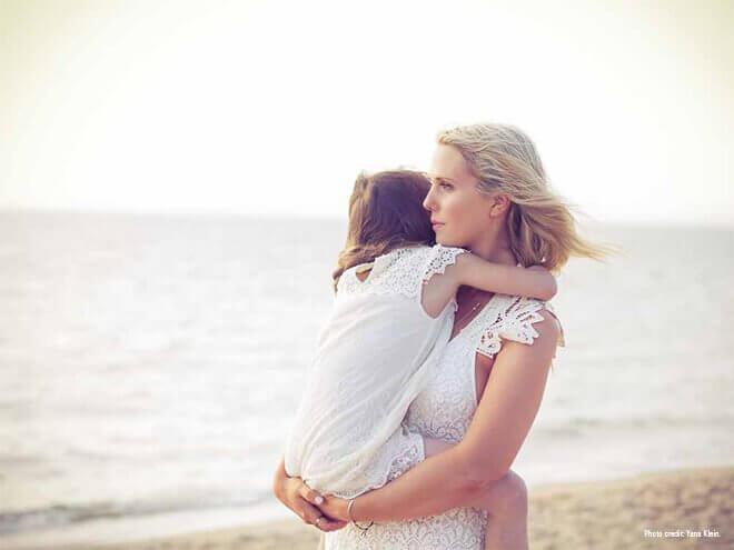 kumsalda kucağında kızını tutan anne