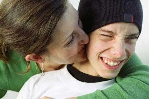 siyah bere takmış oğlunu öpen anne