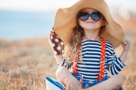 sahilde şapkalı ve gözlüklü çocuk
