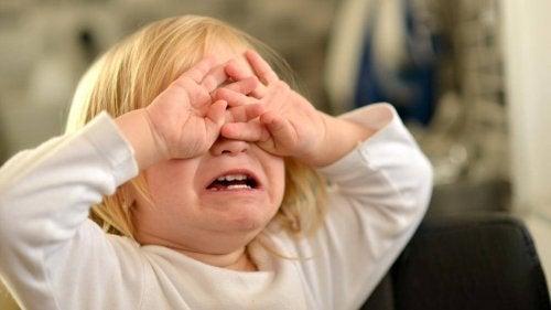 gözlerini kapayarak ağlayan çocuk